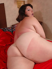 Curly chubby mom spreading on the bed in stockings